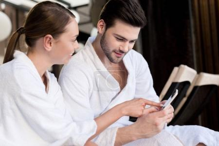 smiling young couple in bathrobes using smartphone together in spa center