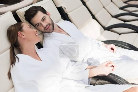 young couple in bathrobes smiling each other while resting together in spa center