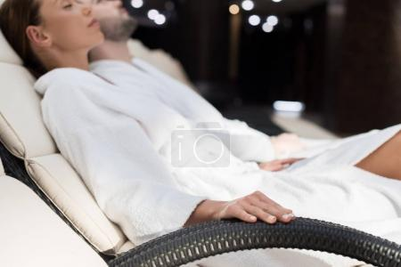 selective focus of couple in bathrobes resting together in spa center