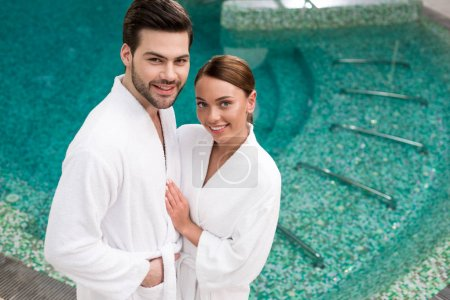 schönes lächelndes junges Paar in Bademänteln, die in der Nähe des Pools im Kurzentrum stehen