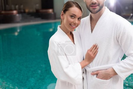 cropped shot of smiling young couple in bathrobes standing near pool in spa center