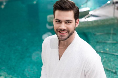 handsome young man in bathrobe smiling at camera while standing in spa center