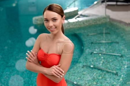 attractive young woman in swimwear standing with crossed arms and smiling at camera in spa center