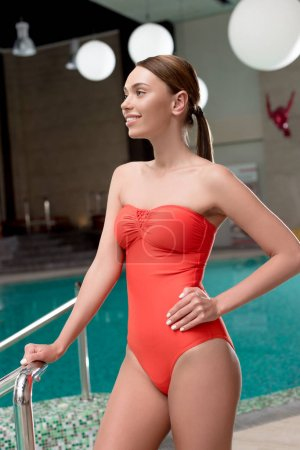 beautiful girl in red swimsuit standing with hand on waist and looking away in spa center