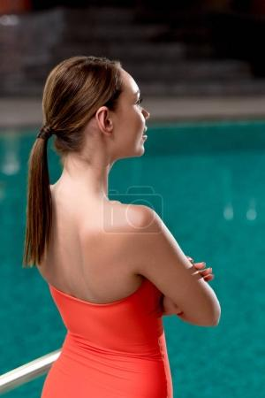 back view of girl in red swimwear standing near pool in spa center