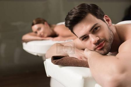 beautiful young couple looking at camera while having massage in spa salon