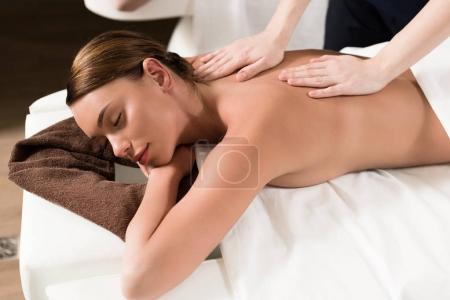 Photo pour Jeune femme détendue avec les yeux fermés ayant massage du corps dans le salon de spa - image libre de droit