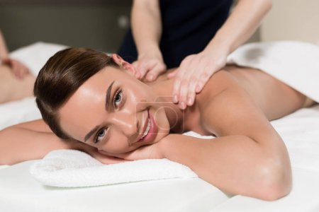 young woman smiling at camera while having body massage
