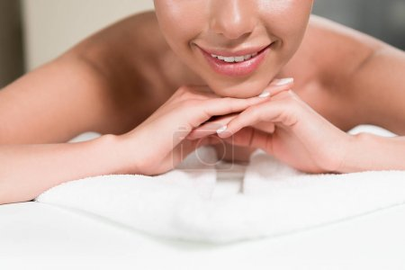 cropped shot of smiling young woman lying on massage table