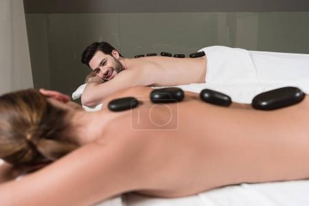 selective focus of couple looking at each other while having hot stones massage in spa center
