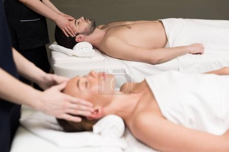 side view of young couple having massage together in spa center