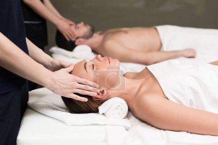 Photo pour Vue de côté de jeunes couples ayant le massage en salon spa - image libre de droit
