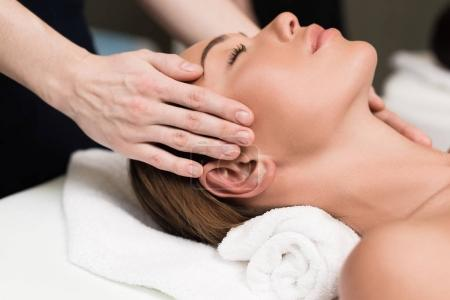young woman relaxing and having head massage in spa salon