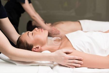 side view of couple having massage in spa salon