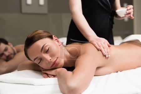 Photo pour Jeune femme avec des yeux fermés, dont le corps massage en salon spa - image libre de droit