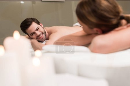 oung couple looking at each other during massage in spa salon