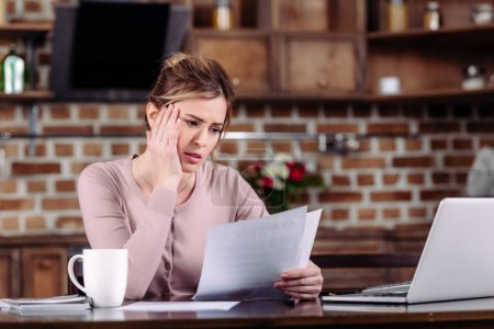 portrait of woman doing paperwork at table at home