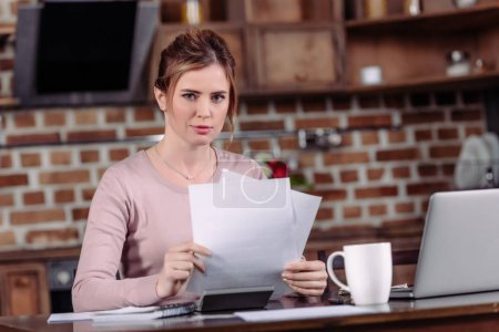 portrait of woman looking at camera while doing paperwork at table at home