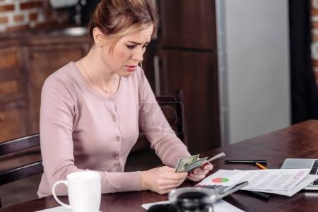 side view of upset woman counting money at table at home, financial problems concept