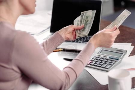 Photo for Cropped shot of woman counting money at table with laptop - Royalty Free Image