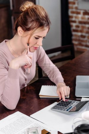 side view of woman making calculations at table at home, financial problems concept