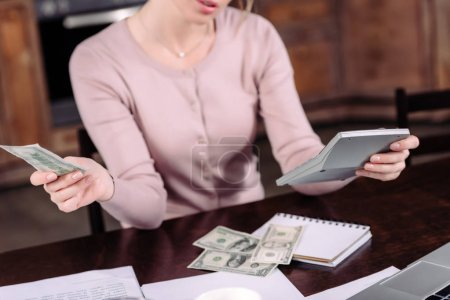 cropped shot of woman counting money at table at home