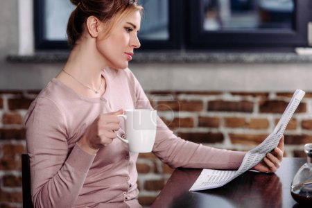 side view of focused woman with cup of coffee reading newspaper at home