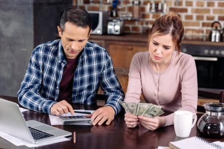 portrait of couple counting money while sitting at table at home