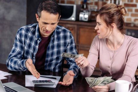portrait of couple counting money while sitting at table at home, financial problems concept