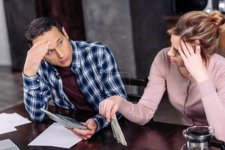 portrait of couple with calculator and money sitting at table at home, financial problems concept