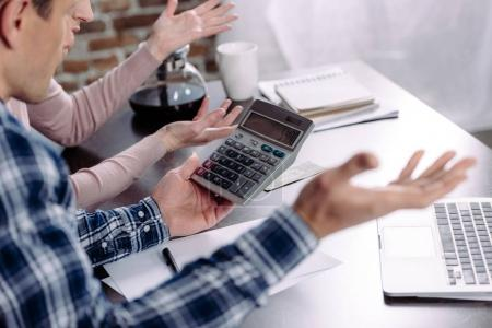 partial view of couple with calculator sitting at table with laptop and papers at home