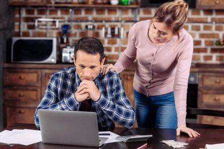 Photo pour Portrait de femme, acclamant haut mari contrarié qu'assis à table avec ordinateur portable à la maison, le concept de problèmes financiers - image libre de droit
