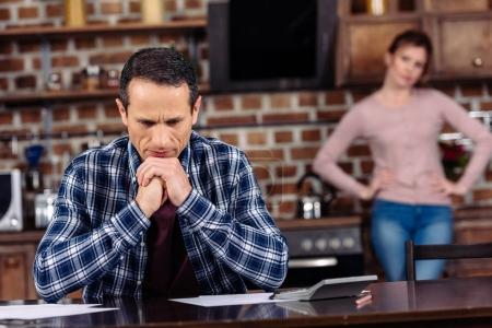 selective focus of pensive man sitting at table and wife standing behind at home, financial problems concept