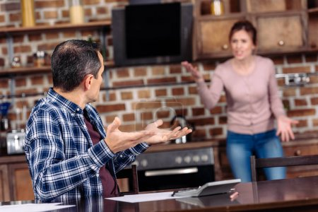 Photo for Selective focus of wife and husband having argument in kitchen at home, financial problems concept - Royalty Free Image