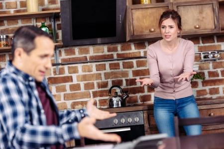 selective focus of wife and husband having argument in kitchen at home, financial problems concept