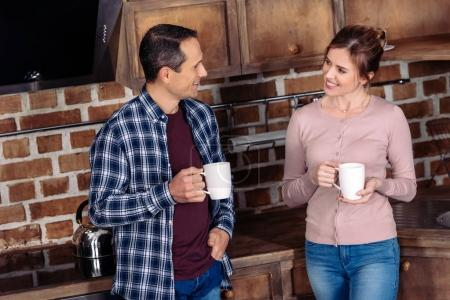 portrait of smiling wife and husband with cups of coffee talking in kitchen at home