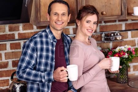 Photo pour Portrait de femme souriante et mari avec des tasses de café dans la cuisine à la maison - image libre de droit
