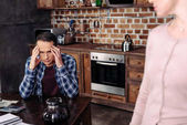 selective focus of woman looking at pensive husband at table at home, financial problems concept