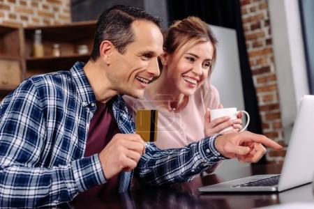 happy couple with credit card and cup of coffee looking at laptop screen at home