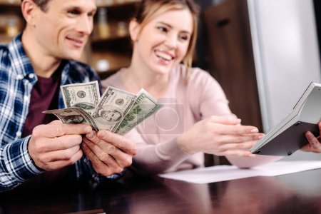 portrait of happy couple counting money together at home