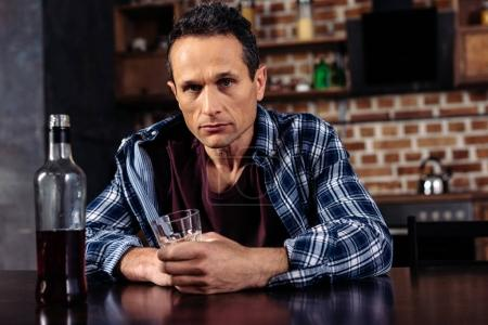 Photo for Man sitting at table with bottle and glass of alcohol at home - Royalty Free Image