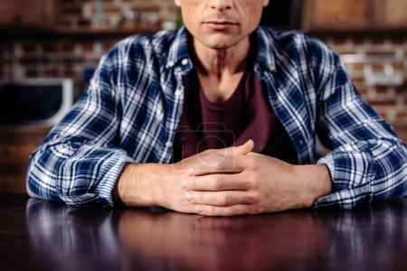partial view of man sitting at table in kitchen at home