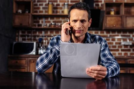 portrait of shocked man talking on smartphone while looking at paper in hand at home