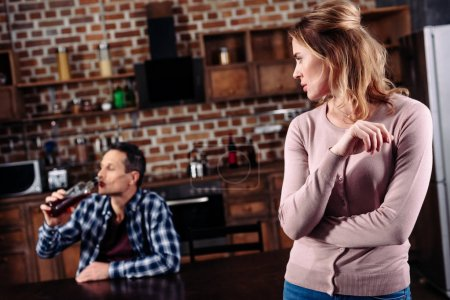 selective focus of woman looking at drunk husband at table in kitchen