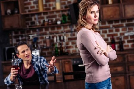 selective focus of woman and drunk husband at table in kitchen