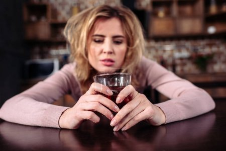Photo for Portrait of drunk woman with glass of alcohol sitting t table at home - Royalty Free Image