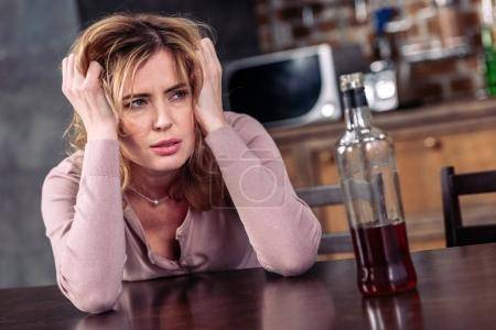 portrait of drunk woman sitting at table with bottle of alcohol at home