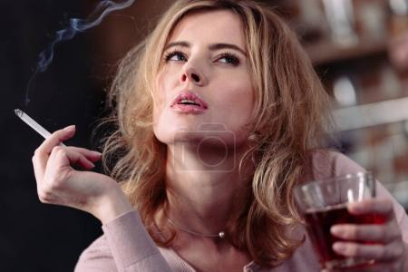 portrait of pensive woman with glass of alcohol and cigarette