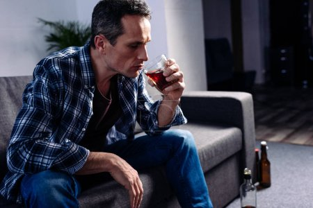 side view of man with glass of alcohol sitting on sofa at home