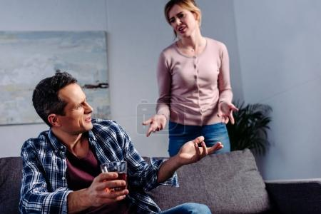 Photo for Man with glass of alcohol sitting on sofa while arguing with wife behind at home - Royalty Free Image